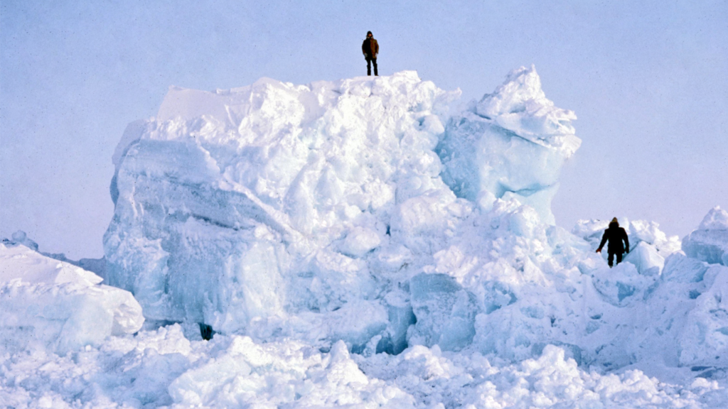 Scientists standing on pressure ridge of ice in Arctic Ocean.