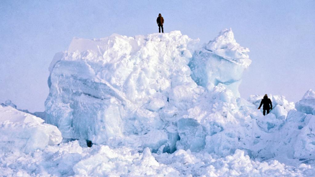 Scientists standing on pressure ridge of ice in Arctic Ocean.